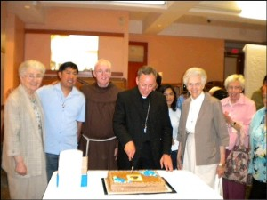 Archbishop Miller accompanied by a Friar and Atonement Sisters while cutting the celebration cake